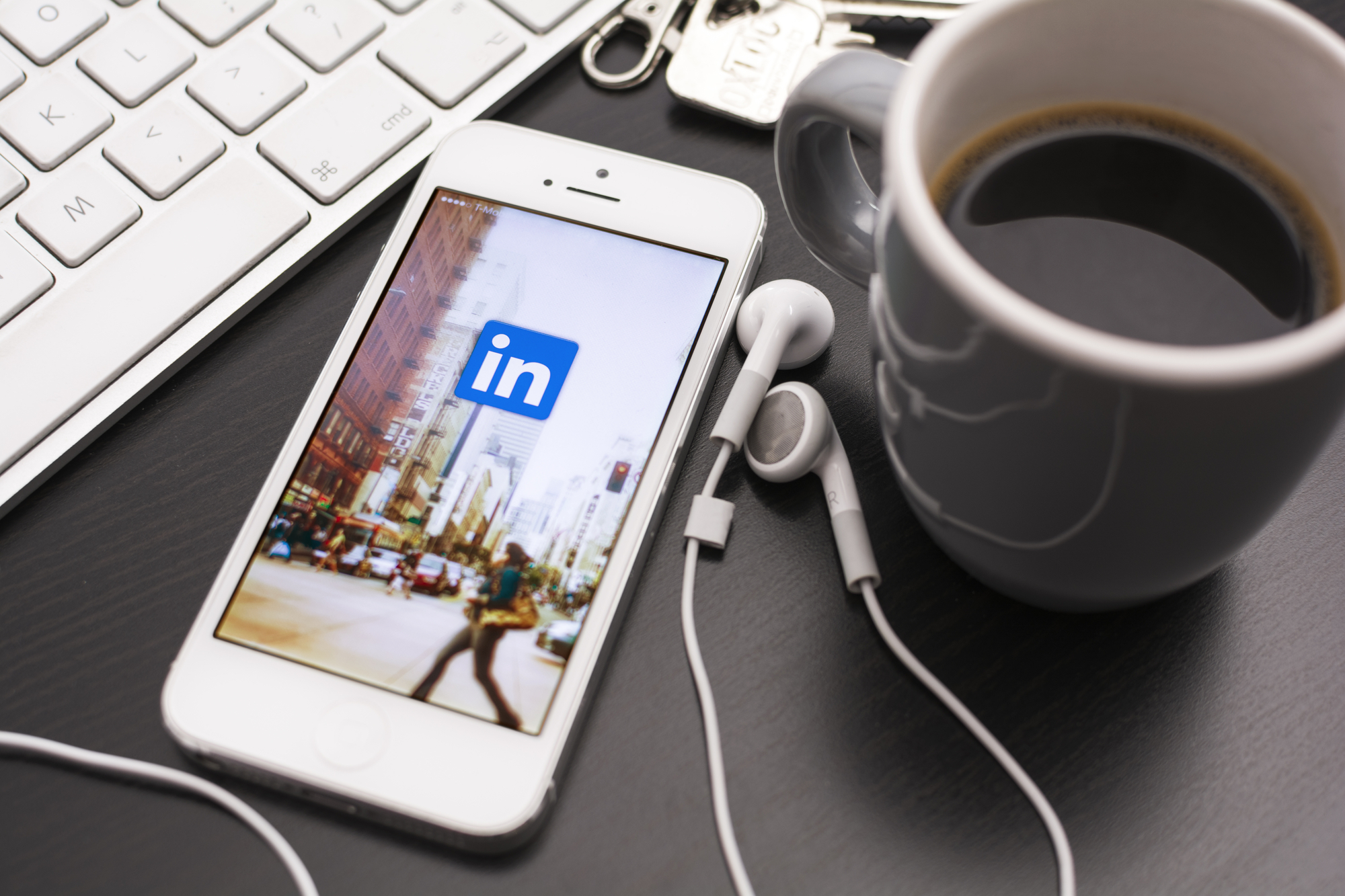 Phone on a desk displaying linkedin